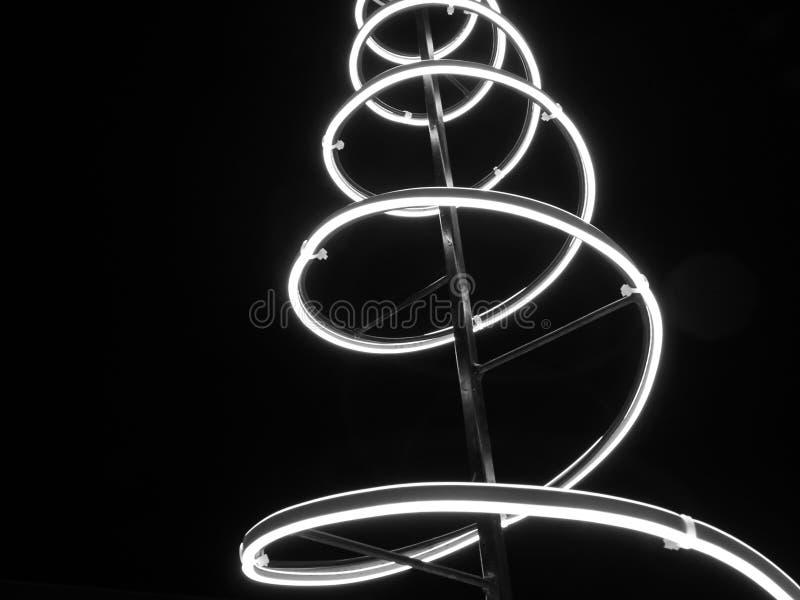 Foto monocromática Instalación navideña espiral de luz, cielo negro nocturno fotografía de archivo