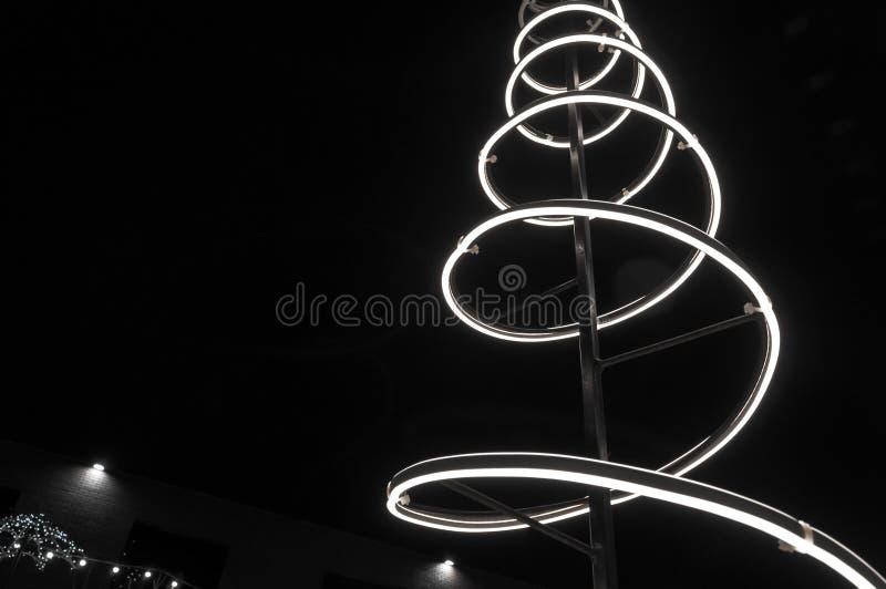 Foto monocromática Instalación navideña espiral de luz, cielo negro nocturno fotos de archivo libres de regalías