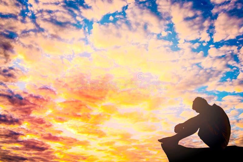 Foto mostrada em silhueta Homem só que senta-se no penhasco fotos de stock