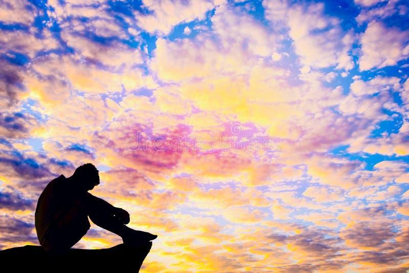 Foto mostrada em silhueta Homem só que senta-se no penhasco imagens de stock