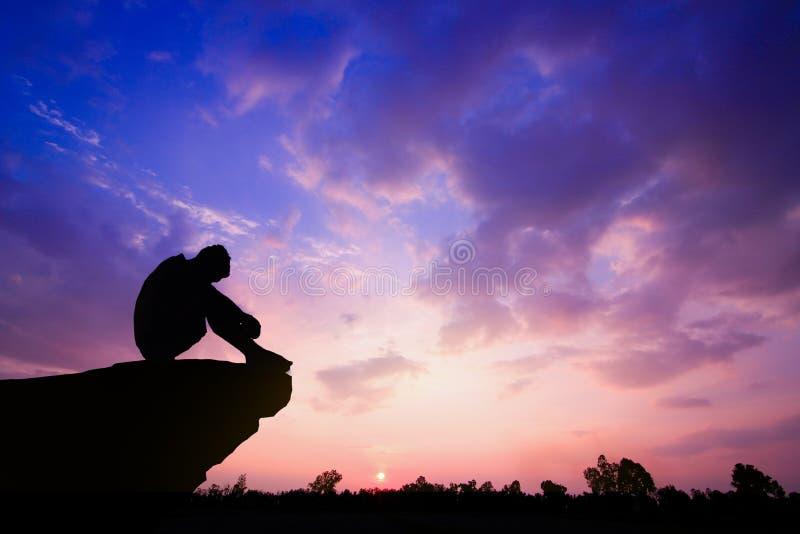 Foto mostrada em silhueta Homem só que senta-se no penhasco foto de stock royalty free