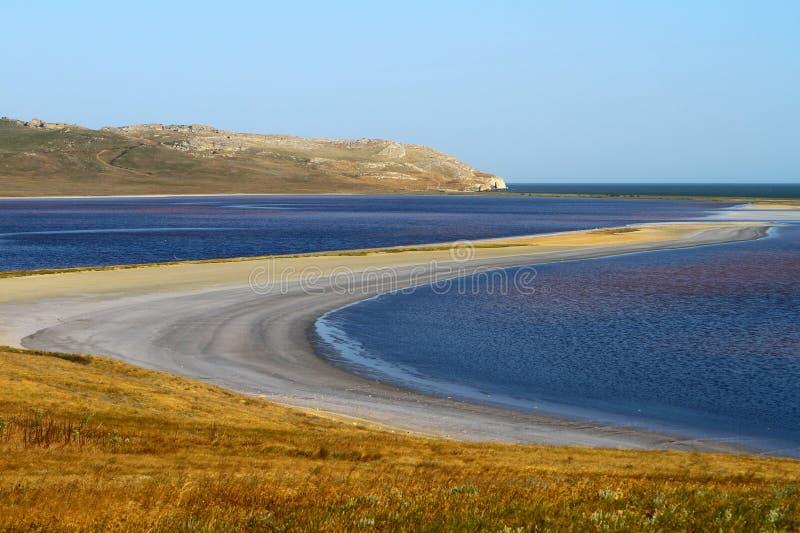 Foto naturale del paesaggio del lago grazioso Kayashskoe in Crimea, alla riva di Mar Nero con acqua salata naturalmente rosa immagini stock libere da diritti