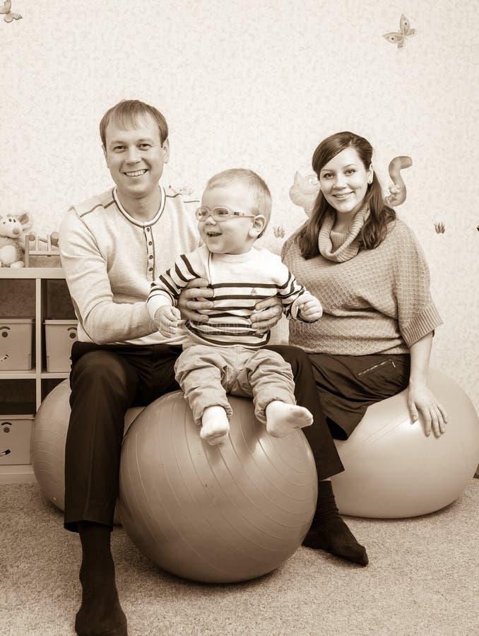 Foto no estilo retro da família nova que salta em bolas da aptidão fotografia de stock