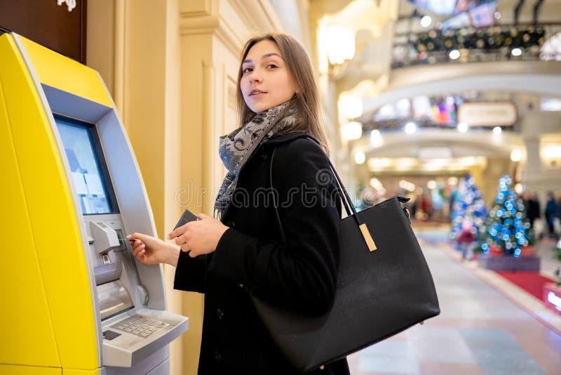 Foto no lado da morena nova com o cartão de banco no ATM foto de stock