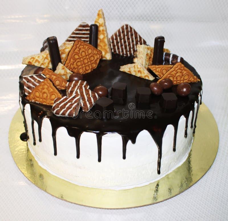 Foto om cake met chocoladekoekjes, snoepjes, wafels, op een gouden substraat stock fotografie