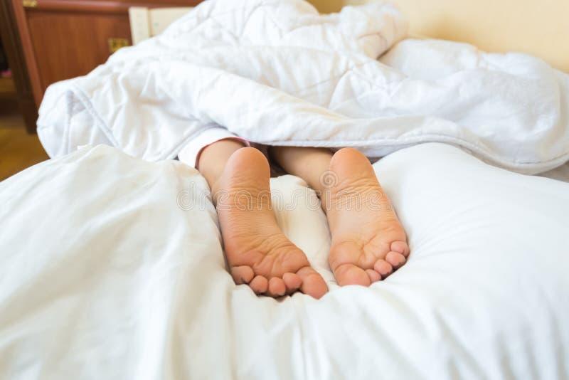 Foto op bed van meisjesvoeten die op hoofdkussen liggen royalty-vrije stock foto's