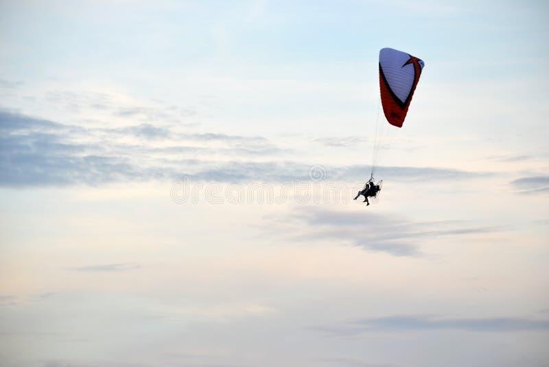 Foto orizzontale del volo di due persone su un aliante in un cielo leggermente nuvoloso della radura di estate fotografie stock libere da diritti