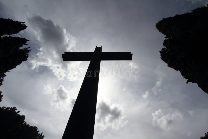 Foto på dödsfall - silhuett av ett stort kors med bakgrundshyllan och typiska hedgefonder royaltyfri fotografi