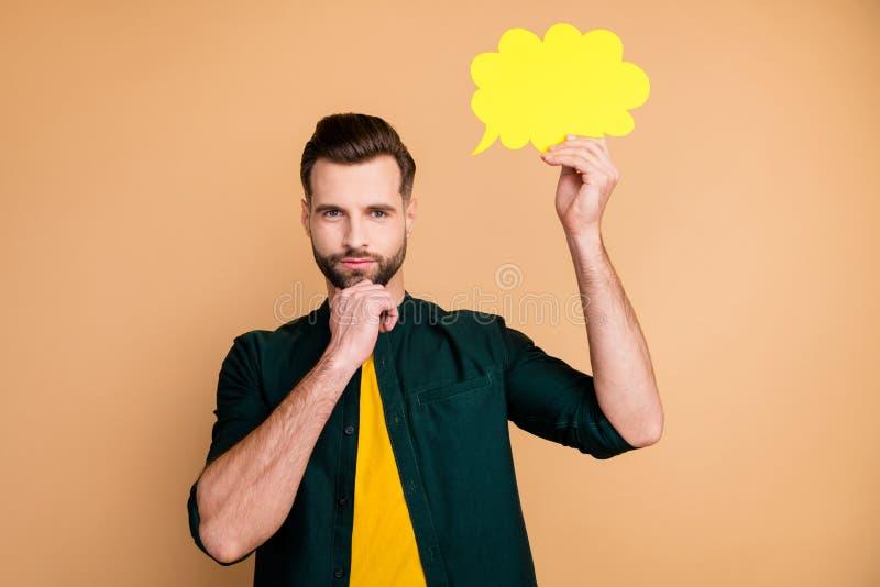 Foto på en snygg kille som håller handpapper i molnet och tänker på dialog och svarar på kreativa människor på chin royaltyfri bild