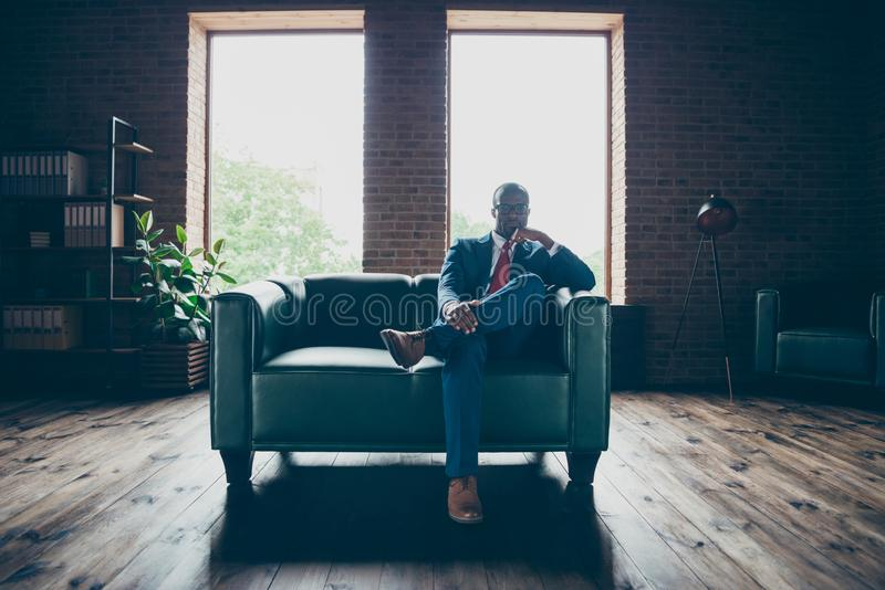 Foto piena del corpo di spec. di seduta di usura del sofà dell'ufficio del tipo macho scuro della pelle e del costume corporativo fotografia stock
