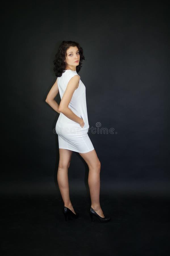 Foto piena di altezza della ragazza attraente in breve vestito bianco e tacchi alti scuri dalla parte posteriore che posa nello s fotografia stock libera da diritti