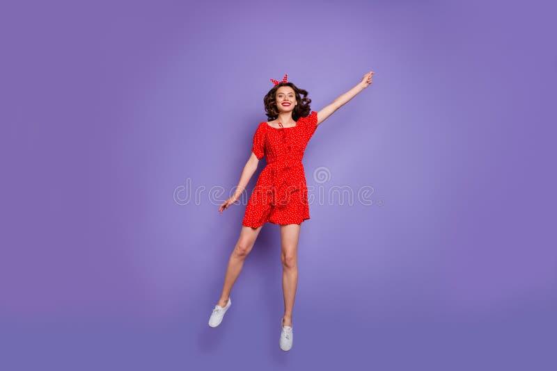 Foto a piena lunghezza di saltellare la donna alta che vola via con il vento indossa il vestito rosso e lo sfondo viola isolato immagini stock libere da diritti