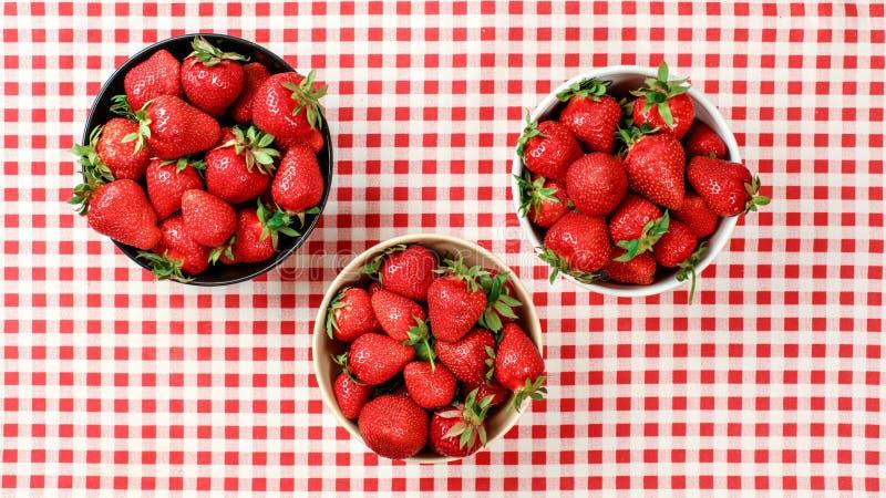 Foto posta piana - tre ciotole con le fragole sulla tovaglia rossa del percalle immagine stock libera da diritti