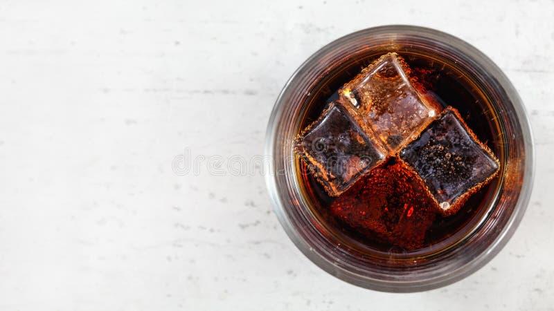 Foto posta piana, vetro con cola, bolle intorno ai cubetti di ghiaccio, sul bordo lavorante bianco, spazio per la parte di sinist immagine stock