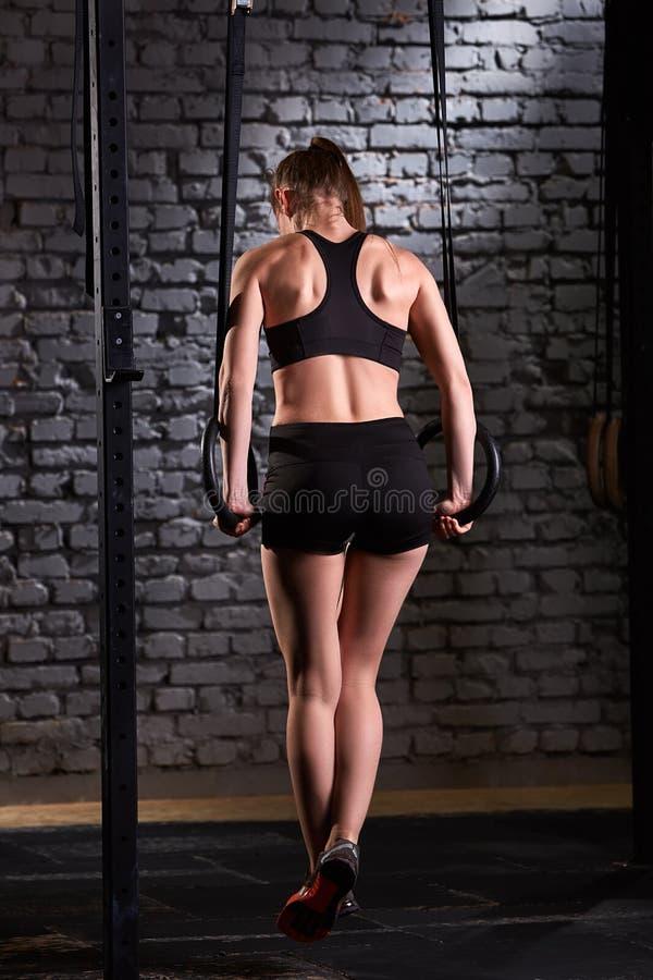 Foto posteriore di giovane donna sportiva che si esercita con gli anelli relativi alla ginnastica nella palestra del crossfit fotografia stock libera da diritti