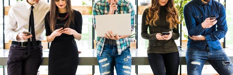 Foto potata del gruppo di amici che stanno sulla tavola e su ognuna uso i suoi divices nella stanza moderna dell'ufficio Insieme  immagini stock