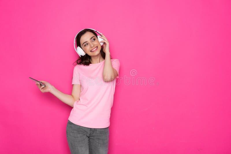 Foto potata delle cuffie d'uso sorridenti e di ascoltare della ragazza castana la musica immagine stock libera da diritti