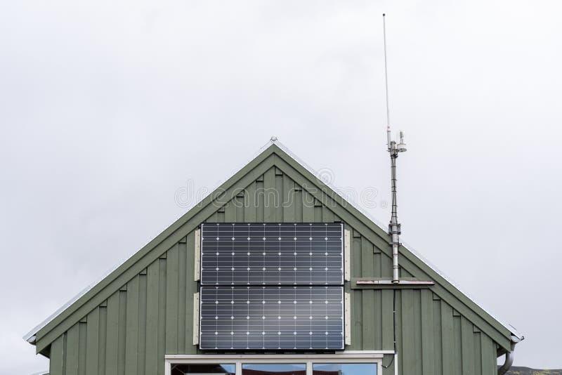 Foto potata di poca serra con il piccolo pannello solare alla parte anteriore della costruzione accanto all'antenna cellulare con immagine stock