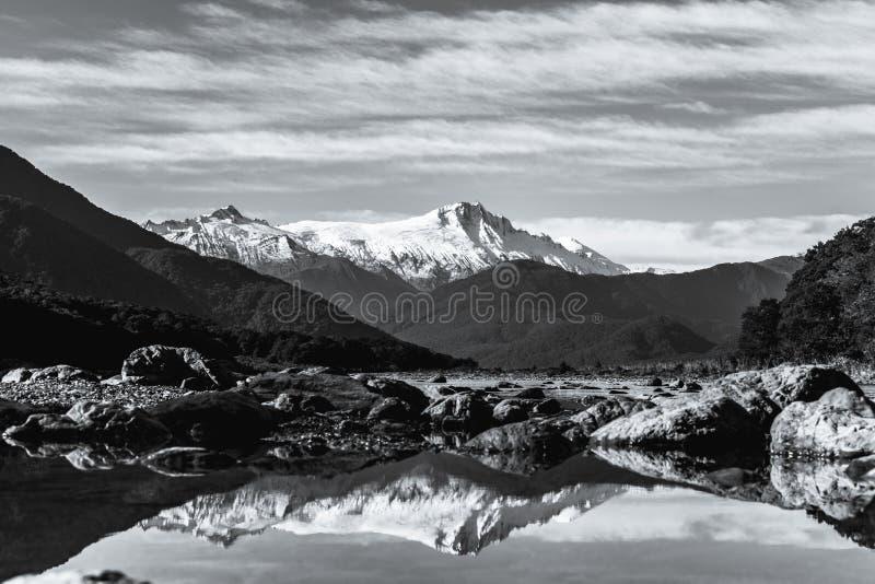 Foto preta e branca Paisagem assombrosa do reflexo da montanha de neve no rio Céu azul e nublado I fotos de stock