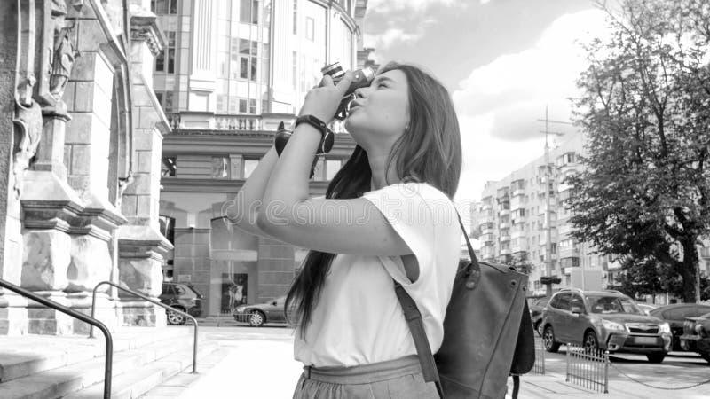 Foto preto e branco da menina à moda que faz fotos na rua com câmera do vintage imagens de stock royalty free