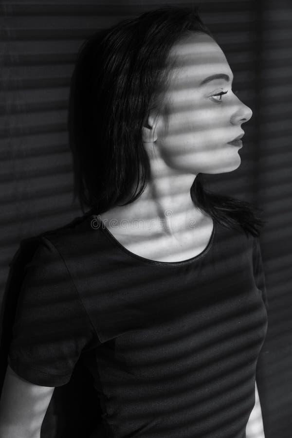 Foto preto e branco da menina Branco preto suporte na máscara do jogo claro a menina nas cortinas de janela foto de stock