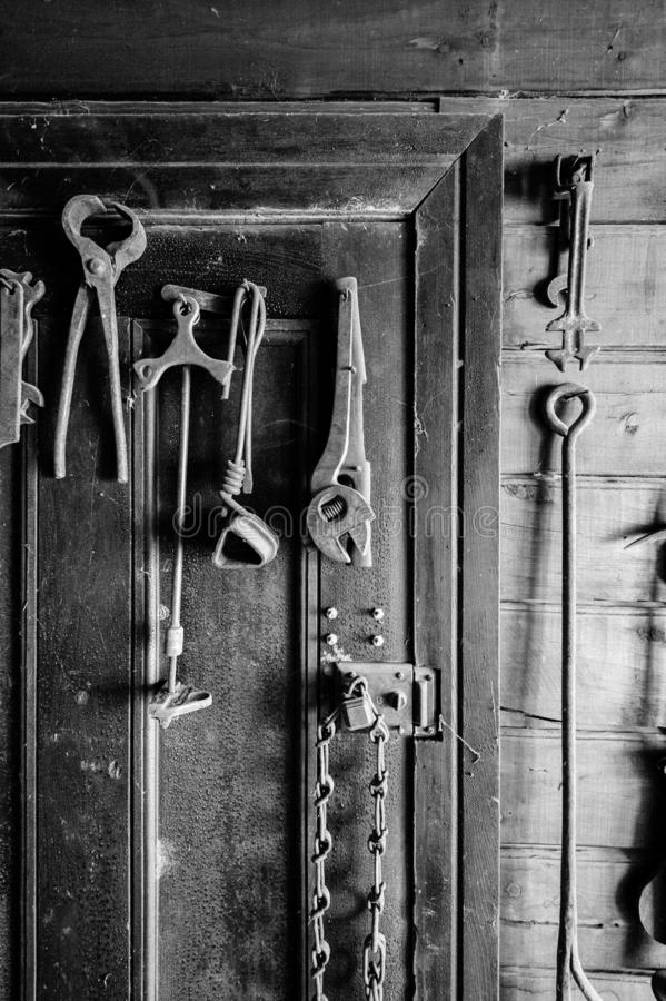 Foto preto e branco das ferramentas velhas penduradas em uma porta foto de stock royalty free