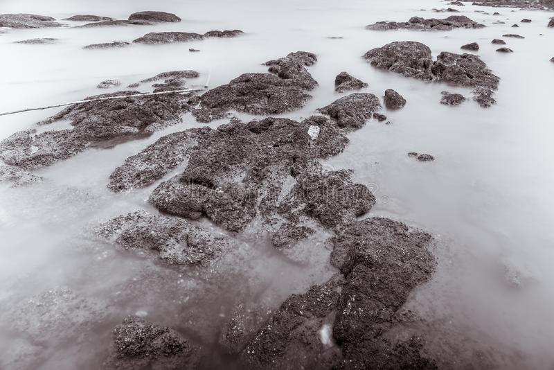 A foto preto e branco de ondas longas da fotografia da exposição nas águas de pedra da praia afia o fundo abstrato do mar tail?nd fotografia de stock royalty free