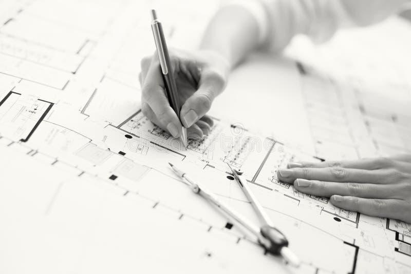Foto preto e branco do arquiteto que trabalha no plano da casa imagens de stock