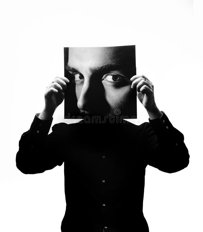 Foto preto e branco do homem na camisa preta que guarda uma foto com a cara de um homem no lugar de sua cara imagens de stock