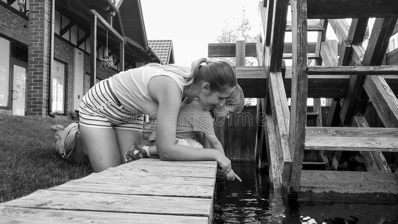 Foto preto e branco do menino bonito da criança com a mãe que ajoelha-se no rio calmo pequeno com moinho de água e que olha a águ foto de stock royalty free