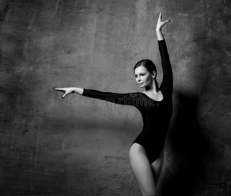 Foto preto e branco do modelo de forma gracioso que levanta sobre o fundo dramático e escuro fotografia de stock royalty free