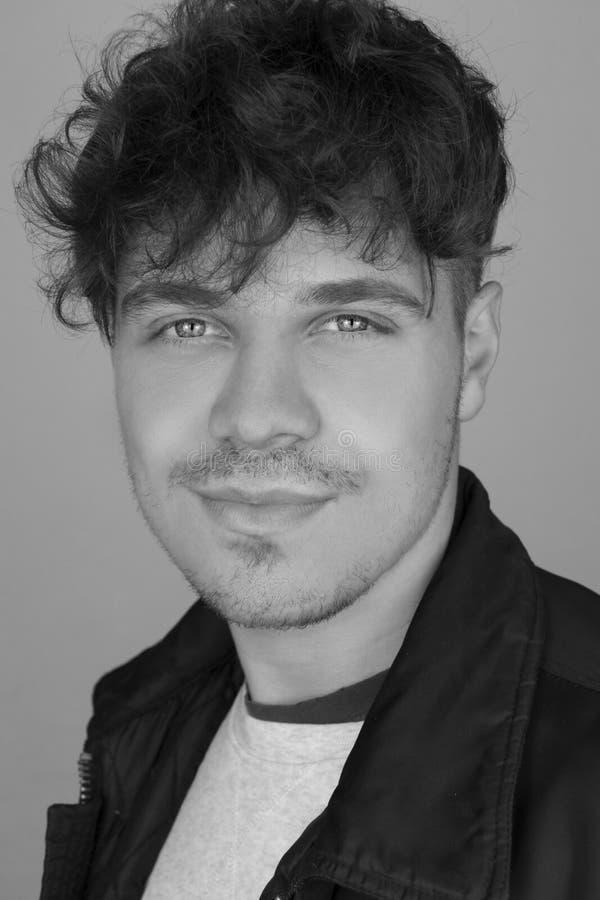 Foto preto e branco do retrato da forma do homem novo e considerável com penteado encaracolado e casaco de cabedal Retrato preto  fotografia de stock royalty free