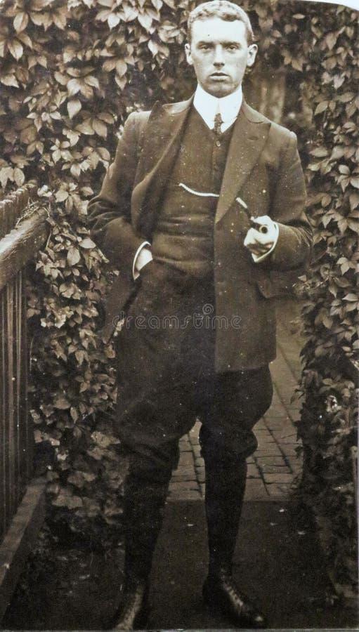Foto preto e branco do vintage de um terno vestindo e de guardar do homem os anos 20 de uma tubulação foto de stock royalty free