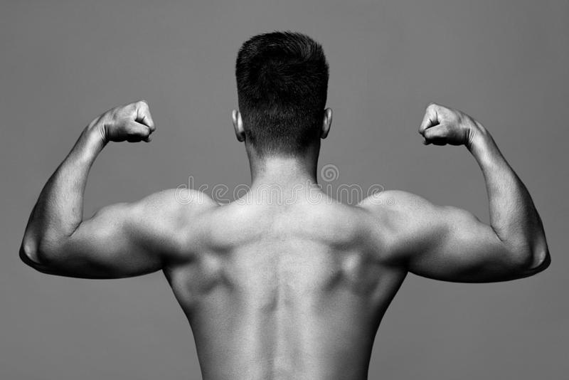 Foto preto e branco, monocromática - homem com corpo muscular e parte traseira forte do atleta do halterofilista com bíceps e fotos de stock