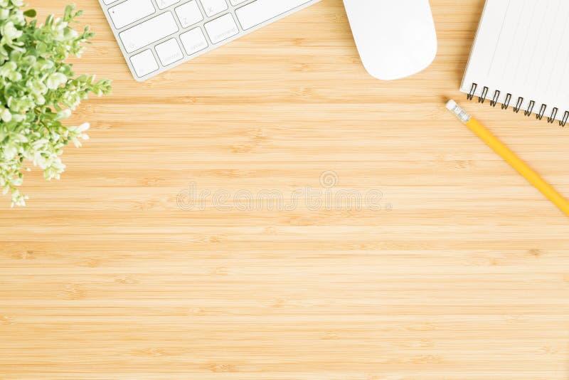 Foto puesta plana del escritorio de oficina con el ratón y el teclado, workpace de la visión superior en la tabla de madera de ba imagen de archivo libre de regalías