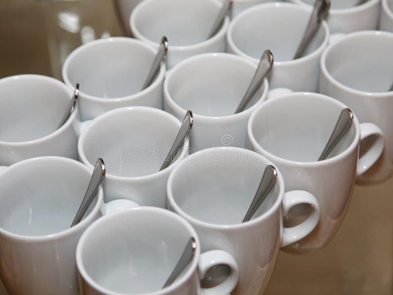 Foto que coloca de cerca filas diagonales juntas 13 tazas blancas de la porcelana con las cucharas del acero inoxidable foto de archivo