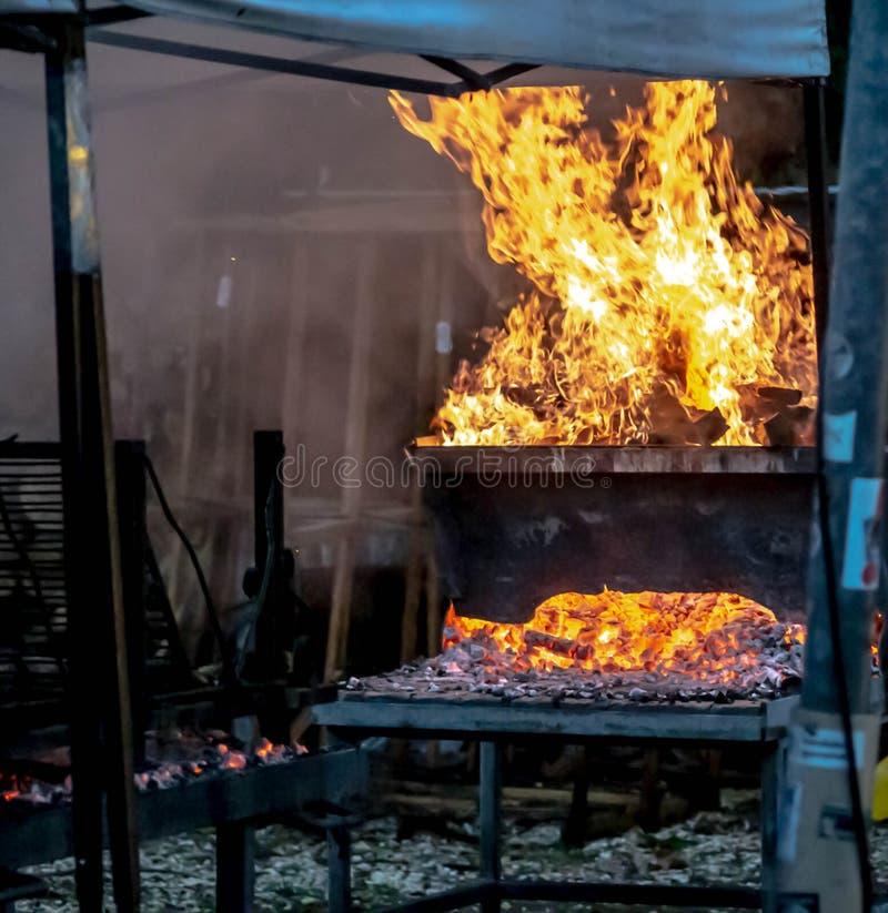 Foto que representa a la gente que hace una carne asada a la parrilla sumergida en humo Fuego y carbones imagenes de archivo