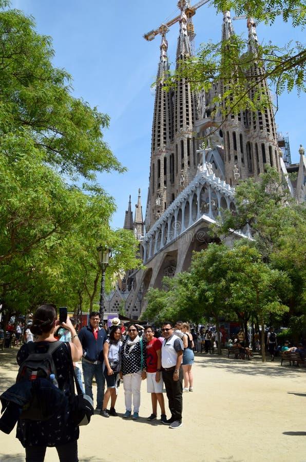 Foto que toma turística de la familia con el La Sagrada Familia en el fondo imagenes de archivo