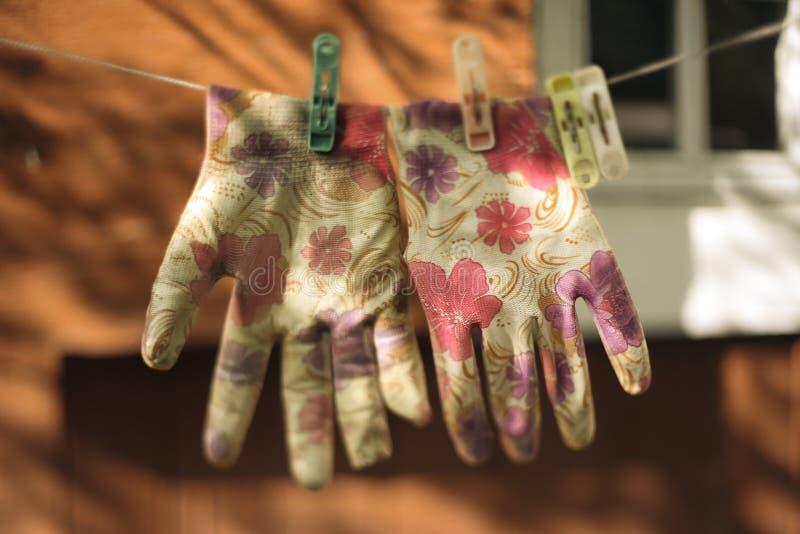 Foto rústica del vintage de los guantes del jardín de la impresión floral que se secan en cuerda fotografía de archivo libre de regalías