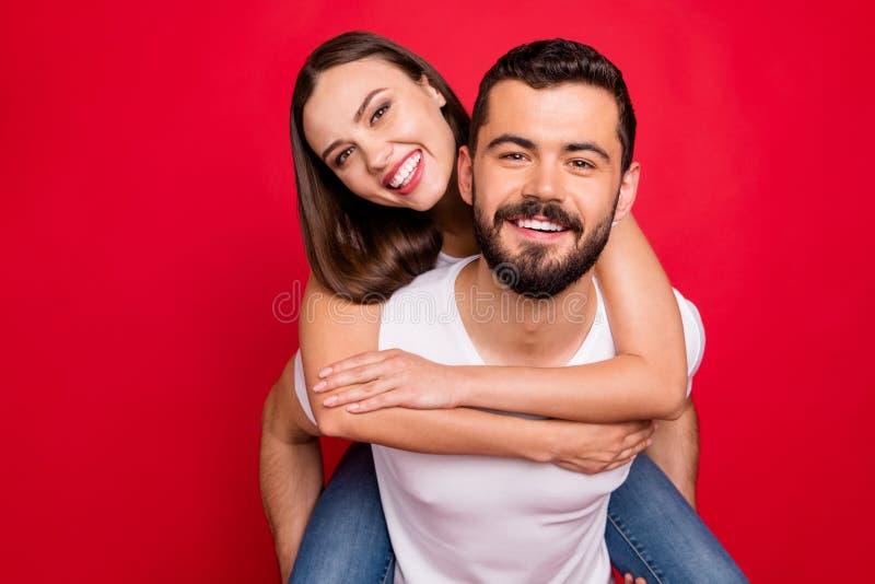 Foto ravvicinata di adorabili carini graziosi e graziosi due persone che indossano jeans denim picgybacked hugs durante l'isolame immagini stock