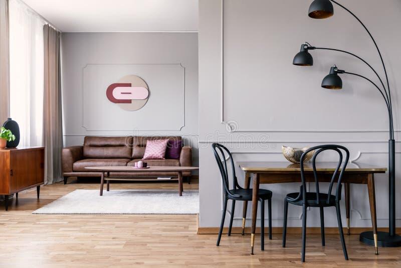 Foto real da lâmpada do metal que está ao lado da mesa de jantar com as duas cadeiras pretas no espaço aberto horizontalmente int fotografia de stock