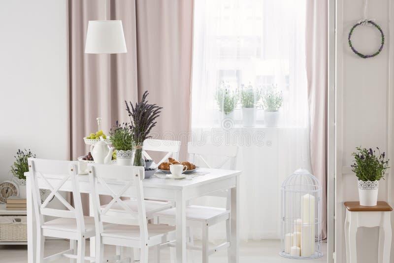 A foto real da tabela branca com alfazema fresca e o café da manhã que estão no interior brilhante da sala de jantar com a janela fotos de stock