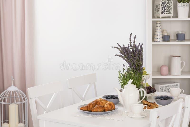 Foto real de la mesa de comedor con las tazas de la lavanda, de las frutas frescas, de los cruasanes, del jarro y de café en inte fotos de archivo libres de regalías