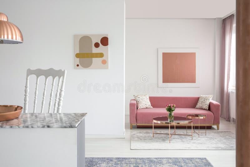 Foto real de pinturas en un interior espacioso de la sala de estar con una mesa de centro rosada del sofá y del cobre foto de archivo libre de regalías
