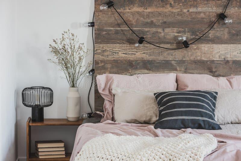 Foto real de um confortável e cor-de-rosa interior de um quarto para uma garota com luzes penduradas em uma cabeça de cama de mad fotografia de stock