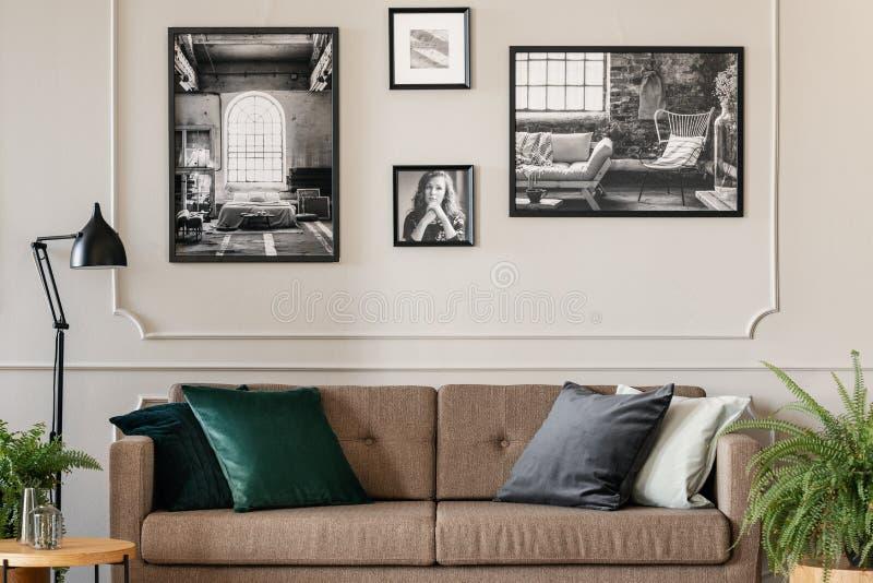 Foto real de um interior acolhedor da sala de visitas com coxins em um marrom, em um sofá retro e em umas fotos na parede branca fotos de stock royalty free