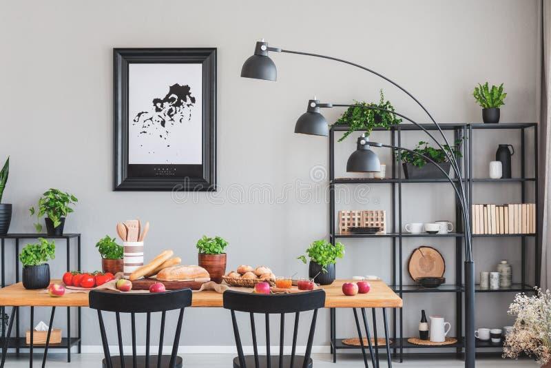 Foto real de um interior diário elegante da sala com uma prateleira, uma lâmpada e uma mesa de jantar pretas com ervas, pão e veg imagens de stock royalty free