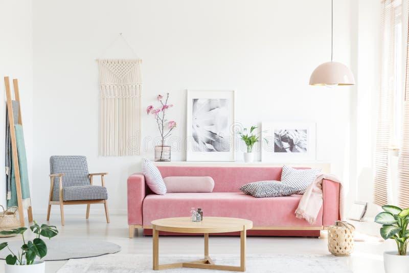 Foto real de um sofá cor-de-rosa com os descansos que estão atrás de uma tabela, foto de stock royalty free