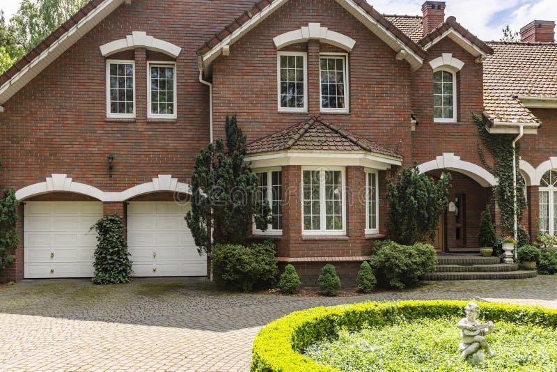 Foto real de uma casa do tijolo com uma janela, as garagens e o redondo de baía imagens de stock royalty free