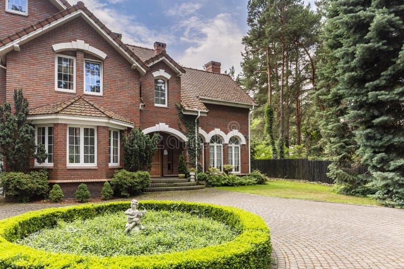 Foto real de uma casa inglesa do estilo e de sua jarda imagem de stock